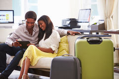 Couple Sitting In Hotel Lobby Looking At Digital Tablet Royalty Free Stock Images