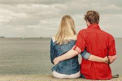Couple sitting hugged on sea shore Stock Images
