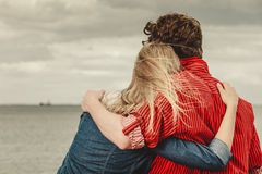 Couple sitting hugged on sea shore. Loving couple spending leisure time together at beach sitting on sea shore hugging rear view Stock Photo