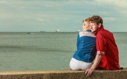 Couple sitting hugged on sea shore Royalty Free Stock Photo
