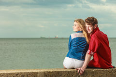 Couple sitting hugged on sea shore. Loving couple spending leisure time together at beach sitting on sea shore hugging rear view Stock Photos