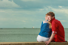 Couple sitting hugged on sea shore. Loving couple spending leisure time together at beach sitting on sea shore hugging rear view Royalty Free Stock Photos