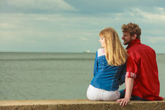 Couple sitting hugged on sea shore. Loving couple spending leisure time together at beach sitting on sea shore hugging rear view Royalty Free Stock Image