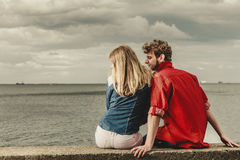 Couple sitting hugged on sea shore. Loving couple spending leisure time together at beach sitting on sea shore hugging rear view Royalty Free Stock Photo