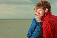 Couple sitting hugged on sea shore. Loving couple spending leisure time together at beach sitting on sea shore hugging side view Stock Images