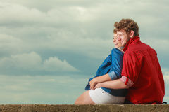 Couple sitting hugged on sea shore. Loving couple spending leisure time together at beach sitting on sea shore hugging side view Royalty Free Stock Photos