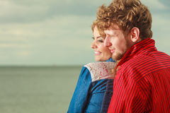 Couple sitting hugged on sea shore. Loving couple spending leisure time together at beach sitting on sea shore hugging side view Stock Photo