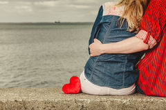 Couple sitting hugged on sea shore. Loving couple spending leisure time together at beach sitting on sea shore with red heart hugging rear view Royalty Free Stock Photography