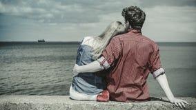 Couple sitting hugged on sea shore Royalty Free Stock Photos