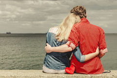 Couple sitting hugged on sea shore. Loving couple spending leisure time together at beach sitting on sea shore with red heart hugging rear view Stock Photos