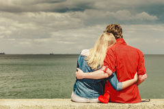 Couple sitting hugged on sea shore. Loving couple spending leisure time together at beach sitting on sea shore with red heart hugging rear view Royalty Free Stock Photos