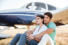 Couple sitting and hugging near small plane Stock Photo