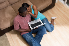 Couple Sitting In Front Of Couch W Computer-Horiz Royalty Free Stock Photography