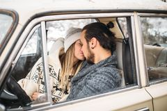 A Valentine couple sitting inside a snow retro car and kissing in a forest. Romantic Beauty girl in a hat and handsome. A couple sitting inside a snow car and Royalty Free Stock Photography