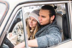 A Valentine couple sitting inside a snow retro car and kissing in a forest. Romantic Beauty girl in a hat and handsome. A couple sitting inside a snow car and Stock Photo