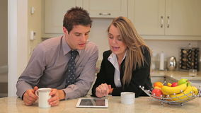 Couple sitting in the kitchen with tablet pc Royalty Free Stock Photo