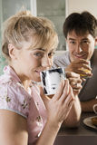 Couple sitting in kitchen, woman drinking from mug, man holding glass, smiling, close-up, portrait Stock Image