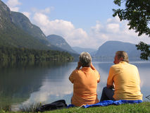 A couple sitting by the lake Stock Images