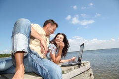 Couple sitting by a lake Royalty Free Stock Images