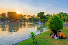 Couple sitting by the lake in Chatuchak park Royalty Free Stock Photos