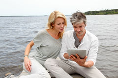 Couple sitting by the lake with tablet stock images