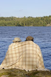 Couple sitting by a lakeside with blanket around shoulders. royalty free stock photography