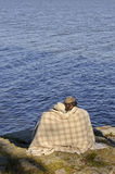 Couple sitting by a lakeside with blanket around shoulders. royalty free stock photos
