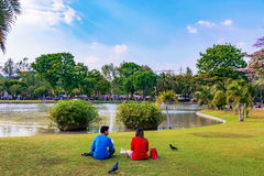 Couple sitting lakeside in Chatuchak park royalty free stock images