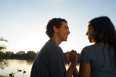 Couple sitting lakeside at a park - Horizontal Stock Image