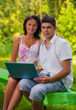 Couple sitting with laptop in park Royalty Free Stock Photo