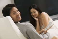 Couple sitting by large flat screen television portrait Royalty Free Stock Photography