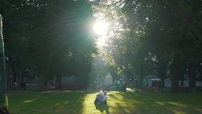 Couple sitting on the lawn in the city stock video footage