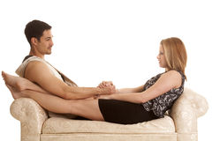 Couple sitting legs out on bench facing Royalty Free Stock Photo