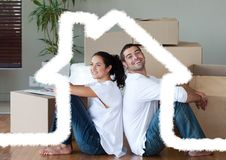 Couple sitting in living room against house outline in background. Digital composition of couple sitting in living room against house outline in background stock photo