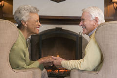 Couple sitting in living room by fireplace royalty free stock image
