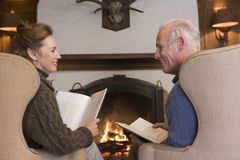 Couple sitting in living room by fireplace Stock Photo