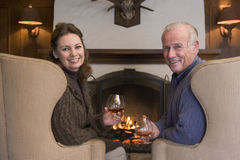 Couple sitting in living room by fireplace Royalty Free Stock Photography