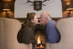 Couple sitting in living room by fireplace kissing Stock Photography