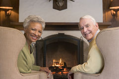 Couple sitting in living room by fireplace smiling Royalty Free Stock Photo
