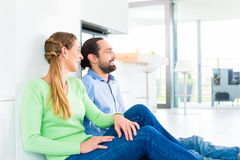 Couple sitting on living room floor enjoying view Royalty Free Stock Images