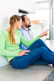Couple sitting on living room floor enjoying view Royalty Free Stock Photos