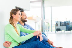 Couple sitting on living room floor enjoying view Royalty Free Stock Photography