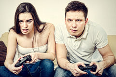 Couple sitting in living room and play video games on console o. Young couple sitting in living room and play video games on console or pc with joysticks while Royalty Free Stock Images