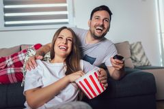 Couple sitting on a living room sofa, watching TV and eating popcorn royalty free stock images