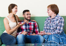 Couple sitting in living room and talking with mother Stock Photo