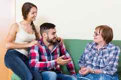 Couple sitting in living room and talking with mother Stock Photos