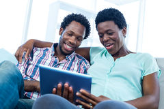 Couple sitting and looking at tablet Stock Photography