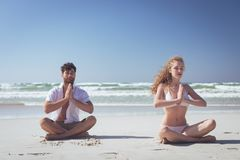 Couple sitting in lotus positions and practicing yoga on beach royalty free stock photos