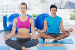 Couple sitting in lotus posture and eyes closed at fitness studio Stock Photos