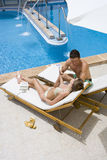 Couple sitting on lounge chairs at poolside.  royalty free stock image